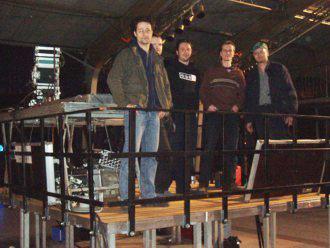 Foto: 5 Männer stehen auf einem Technikerpodest, Tontechnik und Mixer im Hintergrund