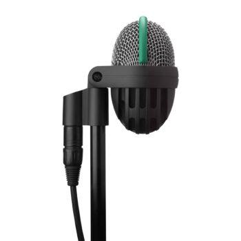 Foto: eiförmiges Mikrofon mit silbernem Korb umrandet von grünem Gummihalbring auf oberer Hälfte und durchbrochene Gehäuse mit feinmaschigem Gewebe auf unterer Hälfte auf schwarzer Halterung mit Stativ